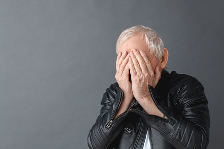 Senior man wearing black leather jacket standing isolated on gray wall covering eyes with hands crying unhappy close-up