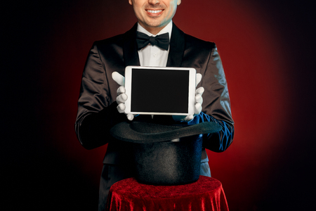 Professional magician wearing suit and gloves standing isolated on black and red background making trick taking digital tablet from top hat on table smiling toothy close-up.