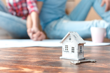 Young husband and wife moving to new place sitting on floor holding hands blurred house model and key close-up