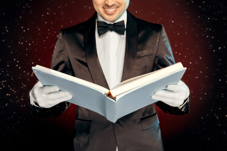 Professional magician wearing suit nd gloves standing isolated on black and red background reading magic book smiling joyful close-up Banque d'images