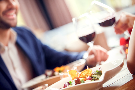 Young man and woman on date in restaurant sitting at table eating vegetable salad close-up holding glasses drinking red wine cheers blurred