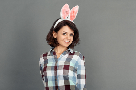 Freestyle. Young woman in bunny ears isolated on grey smiling confident