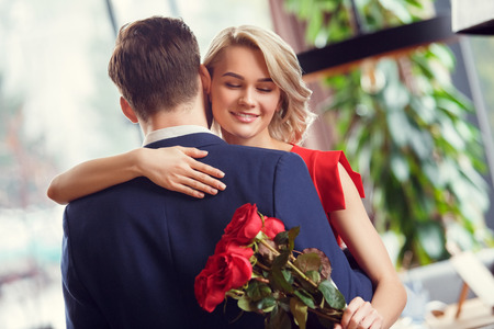 Young couple on date in restaurant dancing holding bouquet woman closed eyes joyful