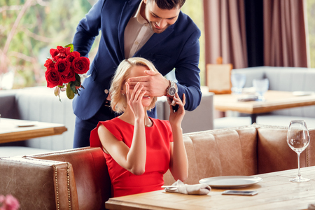 Young couple on date in restaurant man making surpise for woman cheerful