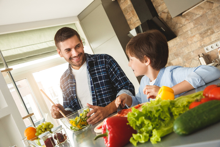 Family at home standing in kitchen making salad together talking smiling cheerful Stock Photo