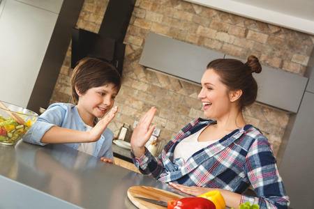 Family at home leaning on table in kitchen together giving high five smiling positive