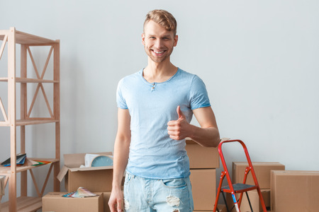 Young man moving to new place standing showing thumb up smiling positive