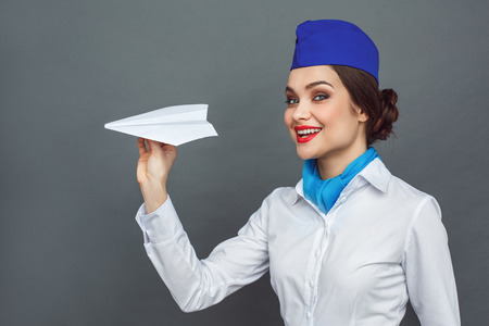 Professional Occupation. Stewardess standing isolated on grey playing with paper plane smiling playful