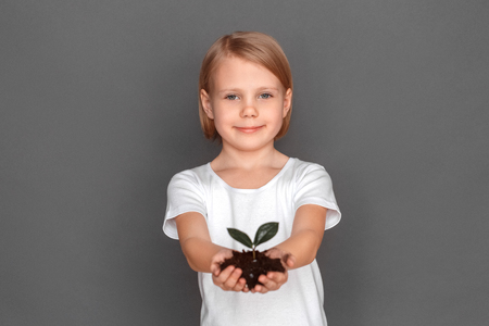 Freestyle. Little girl isolated on grey with plant on soil close-up smiling positive