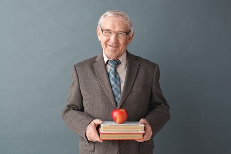 Senior man teacher wearing glasses studio standing isolated on gray with books and apple looking camera friendly Archivio Fotografico - 115542221