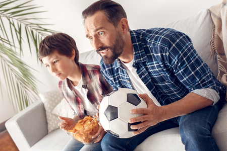 Father and little son at home sitting on sofa boy holding potato chip watching football championship together with dad holding ball nervous