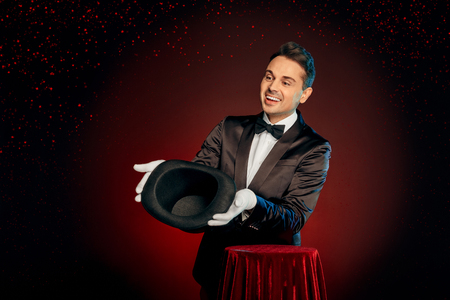 Professional Occupation. Magician in suit and gloves standing isolated on wall making trick showing empty hat to audience friendly Imagens - 115544018