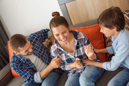 Family at home sitting on sofa in living room together father and son tickling mom cheerful close-up Stock Photo
