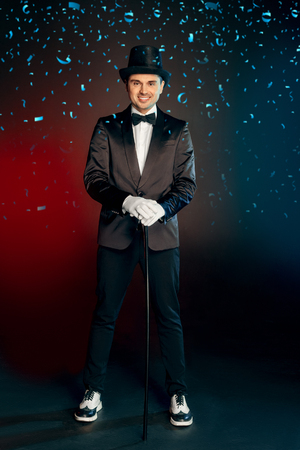 Professional Occupation. Showman in suit gloves and hat standing isolated on wall with cane smiling confident full body shot