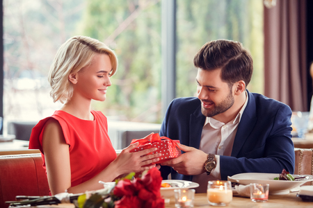 Young couple on date in restaurant sitting man giving gift box to woman smiling happy Banco de Imagens