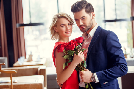 Young couple on date in restaurant standing with bouquet looking camera joyful