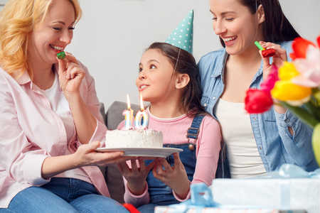 Grandmother mother and daughter together at home birthday sitting girl holding cake smiling close-up