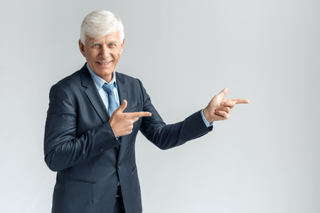 Business Lifestyle. Businessman standing isolated on gray pointing aside smiling playful