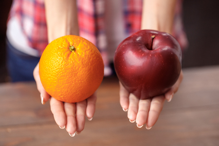 Young girl at kitchen healthy lifestyle holding apple and orange close-up