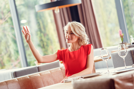 Young woman dining in restaurant sitting waving to waiter cheerful