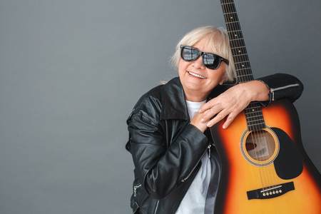 Senior woman in leather jacket and sunglasses studio standing isolated on gray hugging guitar dreaming cheerful Stockfoto