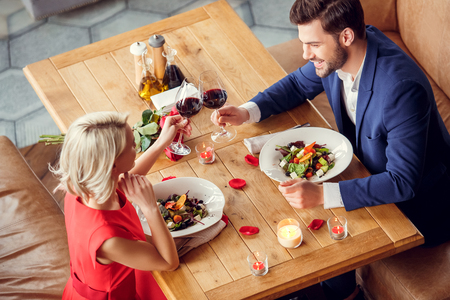 Young couple on date in restaurant sitting eating salad drinking wine talking joyful top view