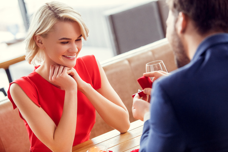 Young couple on date in restaurant sitting woman looking cheerful at proposal ring 写真素材