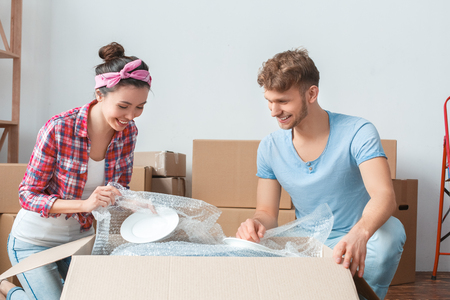 Young couple moving to new place sitting near box unpacking dishes smiling happy