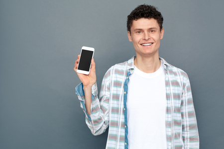 Man isolated on gray wall free style standing holding smartphone joyful