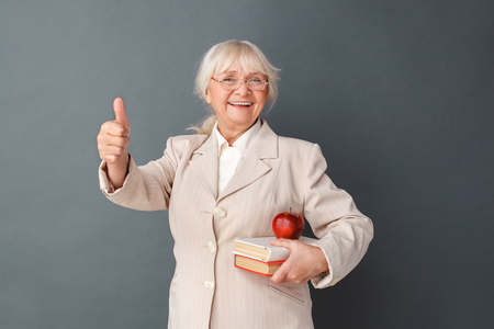 Senior woman in fromal suit and glasses studio standing isolated on gray with books and apple thumb up laughing joyful