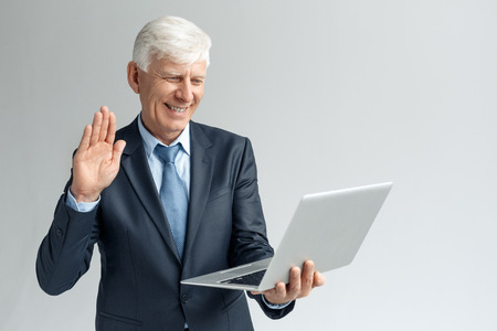 Business Lifestyle. Businessman standing isolated on gray having video call on laptop waving to camera friendly