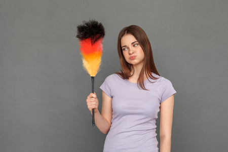 Freestyle. Young girl standing isolated on grey looking at brush for cleaning pouting lips playful Stock fotó