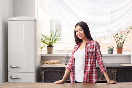 Young girl at kitchen healthy lifestyle leaning on table looking camera relaxed Stock fotó