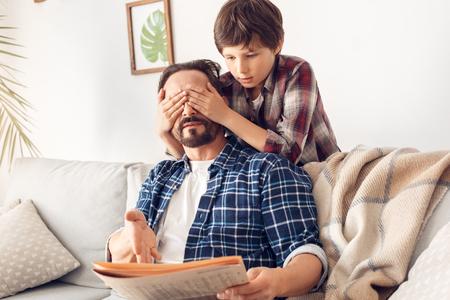 Padre e hijo pequeño en casa niño cubriendo los ojos de papá sentado en el sofá con periódico sorprendente Foto de archivo