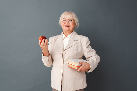 Senior woman in fromal suit and glasses studio standing isolated on gray with books and apple laughing cheerful Archivio Fotografico - 115985889