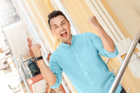 Outdoors leisure. Young man standing on stairs on city street hands up in fists looking camera shouting excited