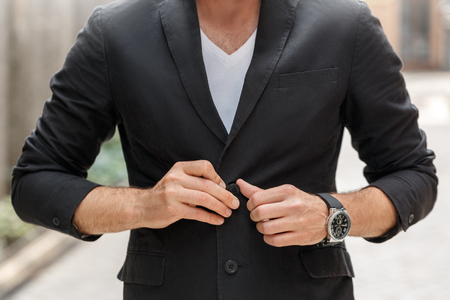 Outdoors leisure. Young man in suit walking on city street button up blazer close-up Banque d'images