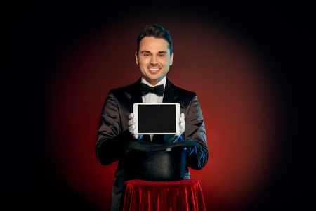 Professional Occupation. Magician in suit and gloves standing isolated on wall making trick taking digital tablet from hat on table smiling friendly Foto de archivo