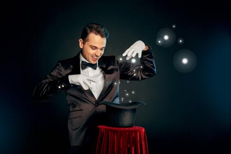 Occupation Professionnelle. Magicien en costume et gants debout isolé sur mur faisant tour avec chapeau sur table souriant ludique