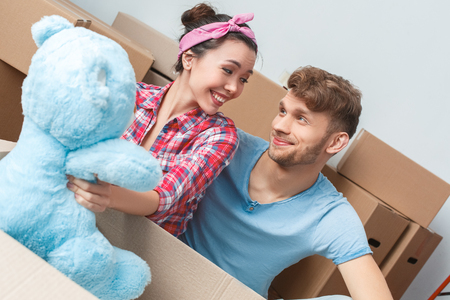 Young couple moving to new place sitting unpacking woman with teddy bear looking at man cheerful