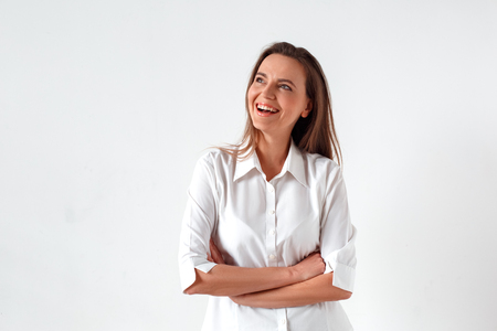 Freestyle. Woman standing isolated on white crossed arms laughing happy inspired with new idea 版權商用圖片