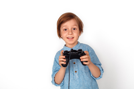 Boy studio standing isolated on grey with game controller playing game excited