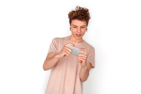 Teenager with earrings studio standing isolated on white playing game on smartphone excited 스톡 콘텐츠
