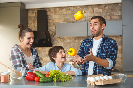 Family at home standing in kitchen together mother and son looking at father juggling laughing joyful Stock fotó