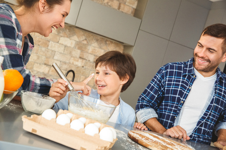 Family at home standing at table in kitchen together mother touching son with hands dirty in flour laughing cheerful