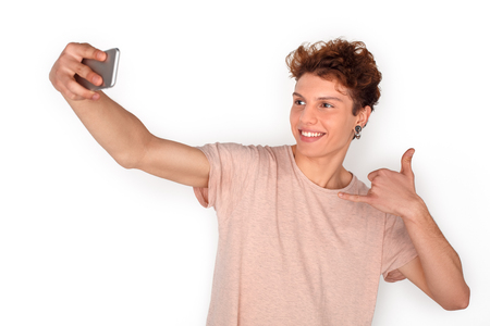 Teenager with earrings studio standing isolated on white taking selfie on smartphone showing call gesture playful
