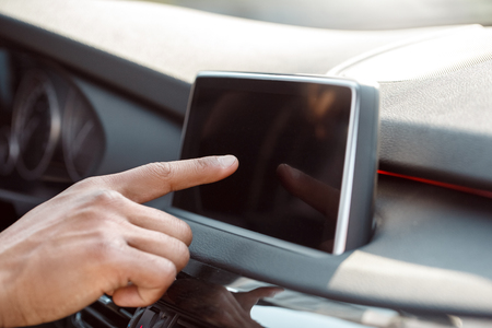 Young businessman driver sitting inside car touchign screen of control panel close-up