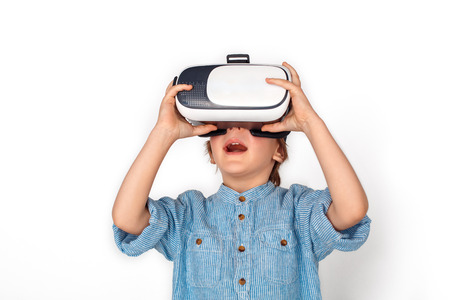 Boy in virtual reality headset studio standing isolated on grey wathcing video impressed Stock Photo