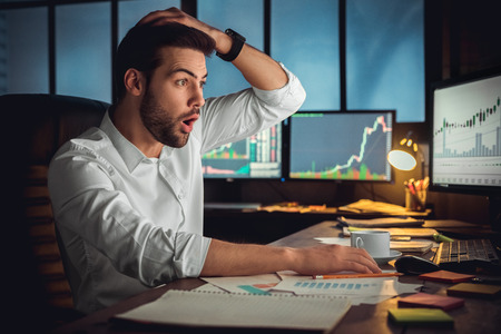 Young male trader at office work concept sitting looking at screen shocked