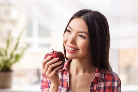 Young girl at kitchen healthy lifestyle standing holding apple looking out the window joyful close-up